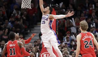 Philadelphia 76ers' Ben Simmons (25) scores off a lob pass from Joel Embiid a  Chicago Bulls' David Nwaba (11) and Lauri Markkanen watch during the second half of an NBA basketball game Thursday, Feb. 22, 2018, in Chicago. The 76ers won 116-115. (AP Photo/Charles Rex Arbogast)