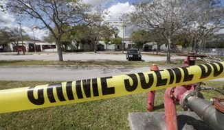 Crime scene tape runs outside Marjory Stoneman Douglas High School in Parkland, Fla., Sunday, Feb. 18, 2018. Authorities opened the streets around the school, which had been closed since a mass shooting on Wednesday. Nikolas Cruz, a former student, was charged with 17 counts of premeditated murder. (AP Photo/Gerald Herbert)