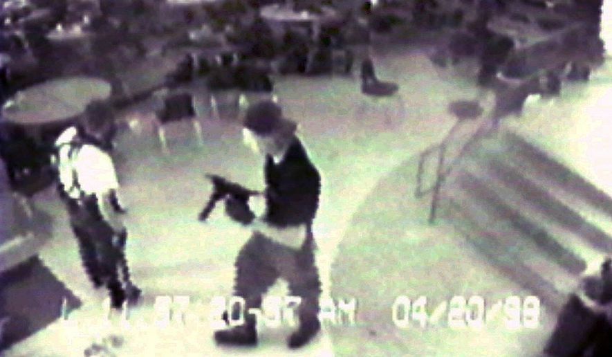 Eric Harris, left, and Dylan Klebold, carrying a TEC-9 semi-automatic pistol, are pictured in the cafeteria at Columbine High School, in Littleton, Colorado, during their April 20, 1999 shooting rampage where they killed a teacher and 12 students. (Associated Press/Jefferson County Sheriff's Department)