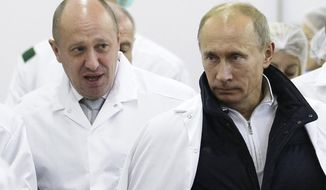 "FILE - In this Monday, Sept. 20, 2010 file photo, businessman Yevgeny Prigozhin, left, shows Russian President Vladimir Putin, around his factory which produces school means, outside St. Petersburg, Russia. One of those indicted in the Russia probe is a businessman with ties to Russian President Vladimir Putin. Prigozhin is an entrepreneur from St. Petersburg who's been dubbed ""Putin's chef"" by Russian media. His restaurants and catering businesses have hosted the Kremlin leader's dinners with foreign dignitaries. (Alexei Druzhinin, Sputnik, Kremlin Pool Photo via AP, File)"