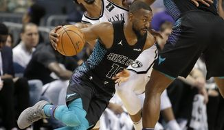 Charlotte Hornets' Kemba Walker (15) gets by a grimacing Brooklyn Nets' Spencer Dinwiddie, who was caught in a screen by Hornets' Dwight Howard (12) during the first half of an NBA basketball game in Charlotte, N.C., Thursday, Feb. 22, 2018. (AP Photo/Bob Leverone)