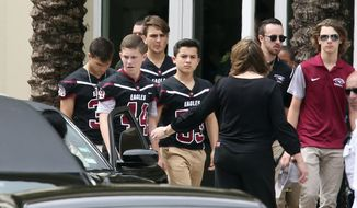 Members of the Marjory Stoneman Douglas High School football team depart the service at the Church by the Glades for Aaron Feis, the football coach who was killed at the school shooting last week, Thursday, Feb. 22, 2018, in Coral Springs, Fla.   Hundreds gathered to remember the 37-year-old assistant football coach and security guard gunned down while helping students to safety during a mass shooting at the high school on Valentine's Day.  (AP Photo/Joel Auerbach)