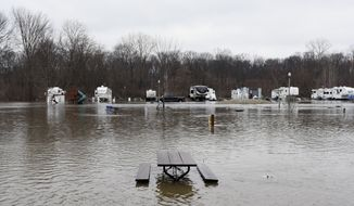 Rising waters from the St. Joseph River floods Shamrock Park in Berrien Springs, Mich., Wednesday, Feb. 21, 2018. Sandbags are holding back floodwaters in parts of Michigan as a storm sweeps across the Midwest and Great Plains, bringing heavy rains, snow and ice.  (Don Campbell /The Herald-Palladium via AP)