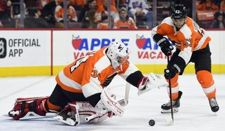 Philadelphia Flyers goalie Petr Mrazek, left, reaches to make a save as Flyers' Shayne Gostisbehere also defends during the first period of an NHL hockey game against the Columbus Blue Jackets, Thursday, Feb. 22, 2018, in Philadelphia. (AP Photo/Derik Hamilton)