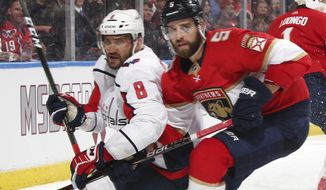 Washington Capitals left wing Alex Ovechkin (8) and Florida Panthers defenseman Aaron Ekblad (5) skate into the corner after the puck during the second period of an NHL hockey game, Thursday, Feb. 22, 2018, in Sunrise, Fla. (AP Photo/Joel Auerbach)