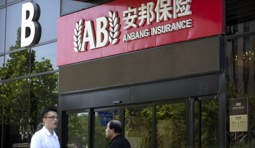 In this June 14, 2017 photo, people walk past an entrance to the Anbang Insurance Group's offices in Beijing. China's insurance regulator said Friday, Feb. 23, 2018 it is assuming management of insurer Anbang, owner of New York's iconic Waldorf Astoria hotel, following the indictment of the company's chairman on charges of economic crimes. (AP Photo/Mark Schiefelbein)