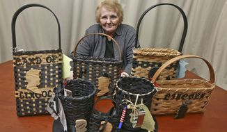 In this Jan. 26, 2018 photo, Donna Johnson poses with her wicker stove top hats and other  Lincoln items at her home in Mount Zion, Ill., that Johnson has created to sell to honor the 16th president, in light of his February 12 birthday. Johnson, a basket weaver fashioned some of her basket creations to look like stovepipe hats, similar to the ones made popular by Lincoln. Johnson adds memorabilia or details, such as cookie cutters, ribbons or recipes. (Clay Jackson/Herald & Review via AP)