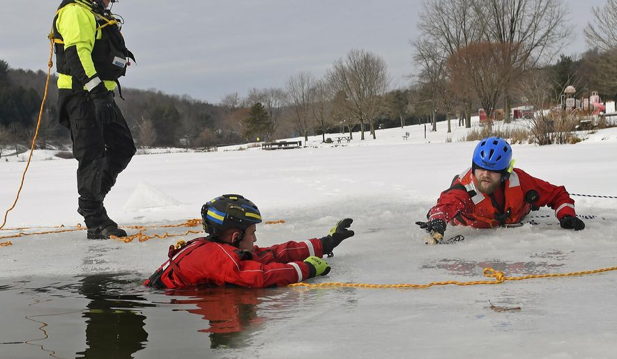 Instructor Scott Grahn, left,  leads an ice and cold water rescue exercise on Saturday, Feb. 10, 2018 at Northmoreland Park Lake in Allegheny Township, Pa.  When a person falls through ice into frigid water, a countdown on their life begins. For those who would rescue them, preparation is vital. That's why, officials said, training sessions like one held Saturday at Northmoreland Park in Allegheny Township are so important.(Jack Fordyce/Pittsburgh Tribune-Review via AP)