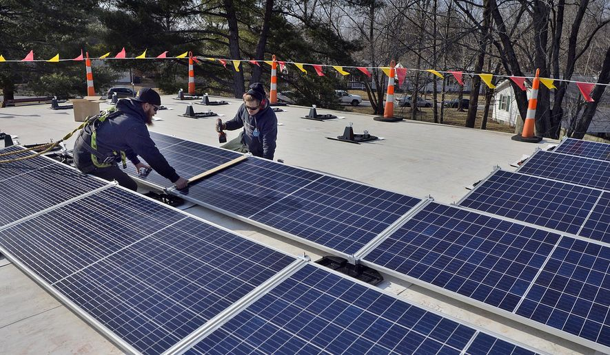 In this Feb. 8, 2018 photo, James Fisher, left, and Tyler Laquinta of Straight Up Solar install  solar panels on the roof of the Church of the Good Shepherd, in Carbondale, Ill. Members of the church are committed to being good stewards of the environment. It is so important that it is written in the church covenant. The congregation moved closer to that goal by installing the solar energy system. (Byron Hetzler/The Southern, via AP)
