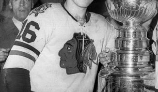 "FILE - In this April 16, 1961, file photo, Chicago Blackhawks hockey player Bobby Hull smiles in the dressing room beside the Stanley Cup after Chicago defeated the Detroit Red Wings, 5-1, to win the NHL Championship, in Detroit. Way back in 1961, Joe Serpico got a pair of game-worn jerseys from Chicago Blackhawks stars Bobby Hull and Glenn Hall for his 10th birthday. It was a gift from his beloved uncle Jerry ""The Barber"" Del Giudice, who served as the team barber for decades. Now Serpico is letting the Hull jersey go as part of an auction while remembering everything he loves about his family and his favorite hockey team.  (AP Photo/File)"