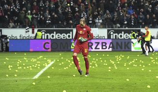 FILE - In this Feb. 19, 2018 file photo Leipzig goalkeeper Lukas Hradecky kicks tennis balls off the pitch prior to the German Bundesliga soccer match between Eintracht Frankfurt and RB Leipzig in Frankfurt, Germany. Fans threw tennis balls onto pitch to protest against the match played on a Monday instead of the weekend. (Fabian Sommer/dpa via AP)