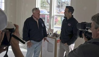 In this Jan. 30, 2018, photo, Texas Land Commissioner George P. Bush, right, and the Federal Emergency Management Agency's Hurricane Harvey Coordinator, Kevin Hannes, left, are surrounded by local media in Nome Texas, while discussing a home damaged in the storm that is being repaired using federal funds. Republican Texas Gov. Greg Abbott tasked Bush's agency with overseeing housing recovery needs after Harvey _ but nearly six months later, victim frustration is growing amid frequent delays and bureaucratic hurdles. (AP Photo/Will Weissert)