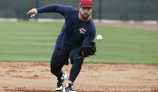 FILE - In this Feb. 16, 2018, file photo, Cleveland Indians first baseman Yonder Alonso gets ready to field a grounder at the Indians spring training facility, in Goodyear, Ariz. Unable to produce big power numbers, Alonso altered his swing last season and the baseball began to fly. After hitting just 39 home runs in his first seven major league seasons, Alonso connected for 28 last year in 142 games for Oakland and Seattle.The Indians are counting on his power surge to continue. (AP Photo/Ross D. Franklin, File)