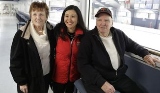 In this Wednesday, Feb. 7, 2018, photo, Kim Muir, center, poses with her parents Al and Lois Muir at the Suburban Ice Arena in Farmington Hills, Mich. Renowned skating coach Kim Muir is returning to South Korea to cheer for clients playing hockey at the Olympic. As a 6-month-old girl, she was left on the streets of Seoul in 1974. A police officer took her to a hospital where she was cleared and unclaimed. The single mother is also taking her two children to Seoul. (AP Photo/Carlos Osorio)