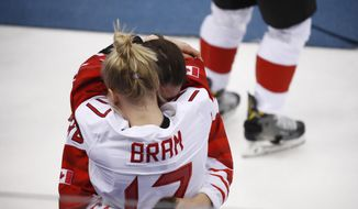 Bailey Bram (17), of Canada, embraces a teammate after losing to the United States in the women's gold medal hockey game at the 2018 Winter Olympics in Gangneung, South Korea, Thursday, Feb. 22, 2018. (AP Photo/Jae C. Hong)