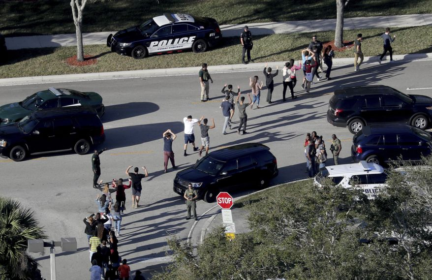 In this Wednesday, Feb. 14, 2018, file photo, students hold their hands in the air as they are evacuated by police from Marjory Stoneman Douglas High School in Parkland, Fla., after a shooter opened fire on the campus. (Mike Stocker/South Florida Sun-Sentinel via AP, File)