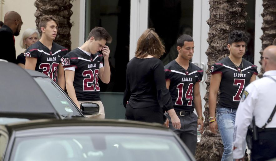 Mourners attend the funeral service for Marjory Stoneman Douglas High School assistant football coach, Aaron Feis. at the Church by the Glades in Coral Springs, Fla., Thursday, Feb. 22. 2018. Football players wearing Stoneman Douglas jerseys carried Feis' casket into the service at the church where family and friends gathered to remember him as loyal and caring. (Mike Stocker/South Florida Sun-Sentinel via AP)