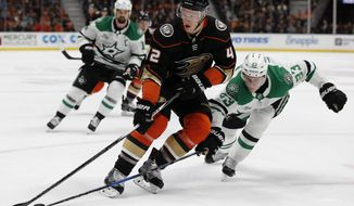 Dallas Stars defenseman Esa Lindell, right, of Finland, reaches in to poke away the puck from Anaheim Ducks defenseman Josh Manson during the second period of an NHL hockey game in Anaheim, Calif., Wednesday, Feb. 21, 2018. (AP Photo/Alex Gallardo)
