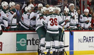 Minnesota Wild right wing Chris Stewart (10) is congratulated by teammates after scoring a goal against the New Jersey Devils during the second period of an NHL hockey game, Thursday, Feb. 22, 2018, in Newark, N.J. (AP Photo/Adam Hunger)