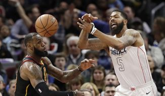 Cleveland Cavaliers' LeBron James, left, and Washington Wizards' Markieff Morris battle for the ball in the first half of an NBA basketball game, Thursday, Feb. 22, 2018, in Cleveland. (AP Photo/Tony Dejak)