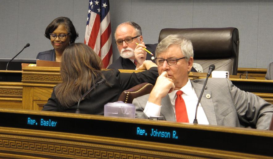 Rep. Dodie Horton, R-Haughton, left, speaks to Rep. Bob Hensgens, R-Abbeville, center, as Rep. Larry Bagley, R-Stonewall, listens to testimony about a Medicaid bill during a hearing of the House Health and Welfare Committee on Thursday, Feb. 22, 2018, in Baton Rouge, La. (AP Photo/Melinda Deslatte)