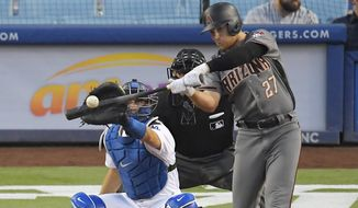 FILE - In this Sept. 4, 2017, file photo, then-Arizona Diamondbacks' Brandon Drury, right, hits a solo home run as Los Angeles Dodgers catcher Austin Barnes watches during the seventh inning of a baseball game, in Los Angeles. New Yankees third baseman Brandon Drury spent the offseason making a half-dozen trips from his home in Las Vegas to Los Angeles to be tutored by the same coaches who remade J.D. Martinez's swing into a home run force.(AP Photo/Mark J. Terrill)