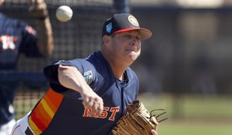 "FILE - In this Feb. 19, 2018, file photo, Houston Astros pitcher Brad Peacock throws live batting practice during spring training baseball practice in West Palm Beach, Fla. Last spring Brad Peacock entered Astros camp worried that he wouldn't make the team. After the best season of his career, the right-hander's spot with the Astros is secure this season, but he's maintained the same mindset he had when his career was on the line. ""I still want to keep that edge on me,"" he said.(AP Photo/Jeff Roberson) **FILE**"