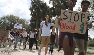 Hundreds of students from Deerfield Beach High School in Coconut Creek, Fla., make their way to Marjory Stoneman Douglas High School in Parkland, Fla., to show support for victims of the recent shooting. (Carline Jean/South Florida Sun-Sentinel via AP)