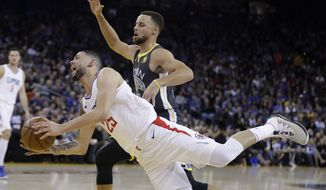 Los Angeles Clippers' Austin Rivers, bottom, is fouled by Golden State Warriors' Stephen Curry on a drive to the basket during the first half of an NBA basketball game Thursday, Feb. 22, 2018, in Oakland, Calif. (AP Photo/Marcio Jose Sanchez)