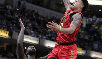 Atlanta Hawks forward John Collins (20) goes up over Indiana Pacers guards Lance Stephenson (1) and Victor Oladipo (4) for a dunk during the second half of an NBA basketball game in Indianapolis, Friday, Feb. 23, 2018. The Pacers defeated the Hawks 116-93. (AP Photo/Michael Conroy)