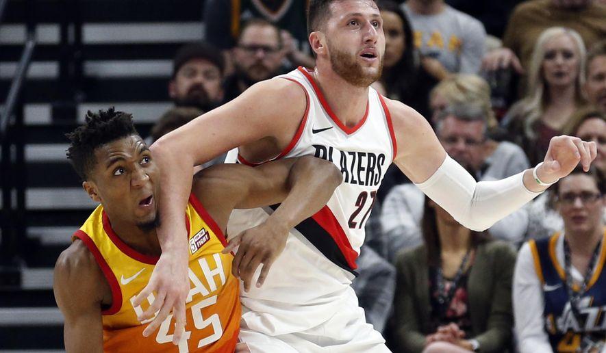 Utah Jazz guard Donovan Mitchell (45) guards Portland Trail Blazers center Jusuf Nurkic (27) during the first half of an NBA basketball game Friday, Feb. 23, 2018, in Salt Lake City. (AP Photo/Rick Bowmer)