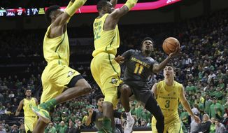 Arizona State's Shannon Evans II, center, shots under pressure from Oregon's Kenny Wooten, left, MiKyle McIntosh and Payton Pritchard, right, during the second half of an NCAA college basketball game Thursday Feb. 22, 2018, in Eugene, Ore. (AP photo/Chris Pietsch)