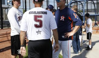Houston Astros manager A.J. Hinch talks with Douglas Stoneman High School's baseball head coach Todd Fitz-Gerald, center, and his son, Hunter Fitz-Gerald, left, during baseball spring training in West Palm Beach, Fla., Friday, Feb. 23, 2018. (Karen Warren/Houston Chronicle via AP)