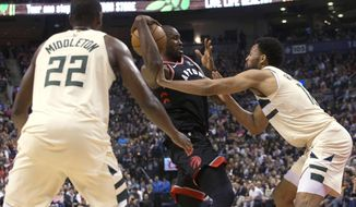 Toronto Raptors forward Serge Ibaka (9) looks to pass under pressure from Milwaukee Bucks forward Jabari Parker (12) and forward Khris Middleton (22) during the first half of an NBA basketball game Friday, Feb. 23, 2018, in Toronto. (Chris Young/The Canadian Press via AP)