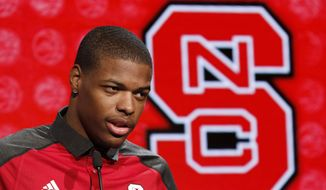 """FILE - In this oct. 26, 2016, file photo, North Carolina State NCAA college basketball player Dennis Smith, Jr. answers a question during the Atlantic Coast Conference media day in Charlotte, N.C. Bank records and other expense reports that are part of a federal probe into college basketball list a wide range of impermissible payments from agents to at least two dozen players or their relatives, according to documents obtained by Yahoo Sports. A balance sheet from December 2015 lists several payments under """"Loan to Players,"""" including $43,500 to Dallas Mavericks guard Dennis Smith, who played one season at North Carolina State in 2016-17. (AP Photo/Bob Leverone, File) **FILE**"""