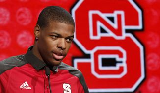 "FILE - In this oct. 26, 2016, file photo, North Carolina State NCAA college basketball player Dennis Smith, Jr. answers a question during the Atlantic Coast Conference media day in Charlotte, N.C. Bank records and other expense reports that are part of a federal probe into college basketball list a wide range of impermissible payments from agents to at least two dozen players or their relatives, according to documents obtained by Yahoo Sports. A balance sheet from December 2015 lists several payments under ""Loan to Players,"" including $43,500 to Dallas Mavericks guard Dennis Smith, who played one season at North Carolina State in 2016-17. (AP Photo/Bob Leverone, File)"