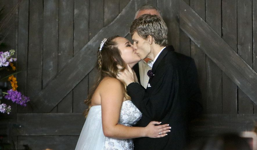 FILE - In this Sunday, Jan. 28, 2018, file photo, Dustin Snyder, 19, kisses his wife Sierra after exchanging wedding vows at the The Big Red Barn in Plant City, Fla. Dustin Snyder, who had been battling a rare form of cancer has died less than a month after marrying his high school sweetheart.(Octavio Jones/Tampa Bay Times via AP, File)
