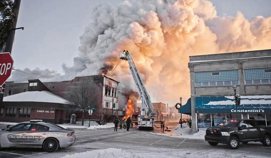 Firefighters battle a fire in downtown Ironwood, Mich., Wednesday, Feb. 21, 2018. The fire claimed at least one life and destroyed two buildings. One of the buildings included two floors of apartments. As of noon, public safety officials wouldn't comment on other injuries, but were working to account for everyone. The cause of the fire remains under investigation. (Jason Juno/The Daily News via AP)