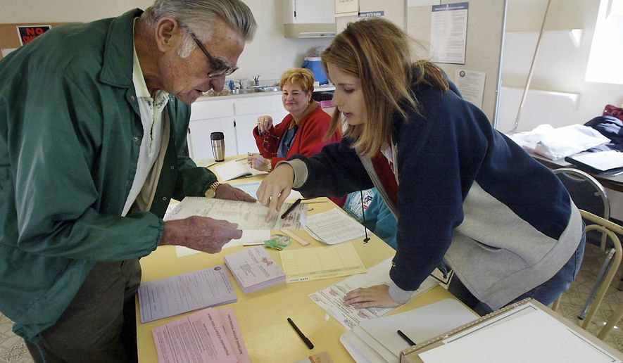 FILE - In this Nov. 2, 2004 file photo, clerk Michelle Gridley, right, assists Bunky Durham as he prepares to cast his ballot at Villa De Oro Recreation Center Club House in Bakersfield, Calif. A federal judge has struck down a redistricting plan for electing supervisors in the county in California's Central Valley. U.S. District Judge Dale Drozd ruled on Friday, Feb. 23, 2018 that election districts in Kern County illegally dilute the voting power of Latinos and deprive them of an opportunity to elect candidates of their choice. (Casey Christie/The Bakersfield Californian via AP, File)