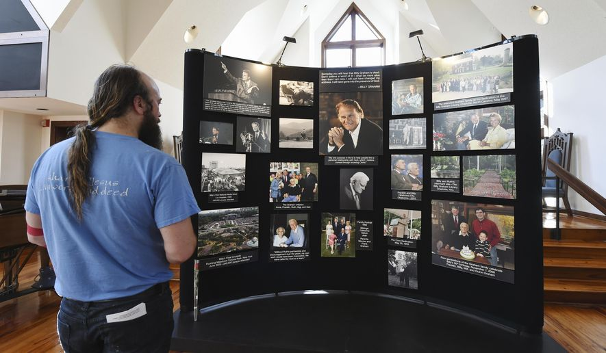 Tracey DeBruhl, of Asheville, N.C., views a memorial display in tribute to the Rev. Billy Graham inside the chapel at the Billy Graham Training Center at the Cove on Wednesday, Feb. 21, 2018, in Asheville. DeBruhl came to pay his respects since he had attended several of Graham's revivals and was inspired by his teachings. (AP Photo/Kathy Kmonicek)