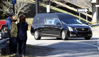 People view and photograph the hearse carrying the remains of Rev. Billy Graham arrives at the Billy Graham Training Center at the Cove on Thursday, February 22, 2018 in Asheville, NC. (AP Photo/Kathy Kmonicek)