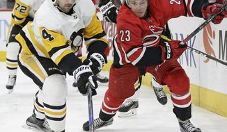 Carolina Hurricanes' Brock McGinn (23) and Pittsburgh Penguins' Justin Schultz (4) chase the puck during the second period of an NHL hockey game in Raleigh, N.C., Friday, Feb. 23, 2018. (AP Photo/Gerry Broome)
