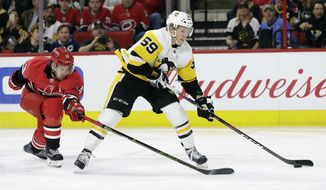 Carolina Hurricanes' Justin Williams (14) reaches for the puck against Pittsburgh Penguins' Jake Guentzel (59) during the first period of an NHL hockey game in Raleigh, N.C., Friday, Feb. 23, 2018. (AP Photo/Gerry Broome)