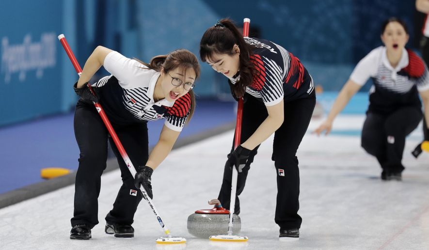 "In this Feb. 21, 2018 photo, South Korea's Kim Seonyeong, left, sweeps ice with teammate during their match against Russian athletes at the 2018 Winter Olympics in Gangneung, South Korea. The team known as the ""Garlic Girls"" came into the Pyeongchang Games as the underdog who few believed would medal. Now they're No. 1 in the rankings. (AP Photo/Aaron Favila)"
