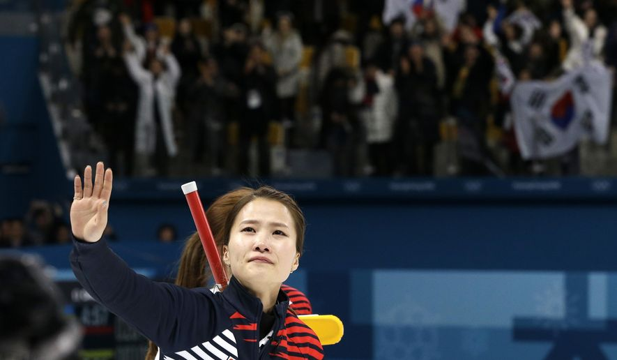 South Korea's skip Kim Eunjung wave to the crowd after winning against Japan in the women's curling semi-final match at the 2018 Winter Olympics in Gangneung, South Korea, Friday, Feb. 23, 2018. (AP Photo/Aaron Favila)