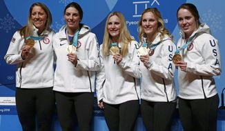 United States' Meghan Duggan, from left, Hilary Knight, Monique Lamoureux-Morando, Jocelyne Lamoureux-Davidson and Maddie Rooney pose for photos with their gold medal in women's hockey at a news conference at the 2018 Winter Olympics in Pyeongchang, South Korea, Friday, Feb. 23, 2018. Twenty years after taking gold when the sport was added to the Olympics, the United States snapped Canada's streak of four straight golds on Thursday. (AP Photo/Peter Morgan)