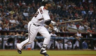 FILE - In this Sept. 27, 2017, file photo, Arizona Diamondbacks' J.D. Martinez watches the flight of his home run against the San Francisco Giants during the ninth inning of a baseball game in Phoenix. The Boston Red Sox have still yet to finalize their contract with prized free agent Martinez. Red Sox manager Alex Cora said Friday, Feb. 23, 2018, that he is not concerned by the delay and is simply focused on preparing the players he already has in camp. (AP Photo/Ross D. Franklin, File)