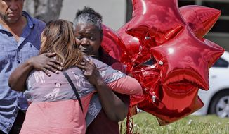 Marjory Stoneman Douglas High School bus driver Pearlie Corker, gets a hug at the school as some teachers return for the first time since the shooting, Friday, Feb. 23, 2018 in Parkland, Fla. Corker arrived at the school as Nikolas Cruz began to shoot students and teachers on February 14th, she stayed on the bus in front of the school praying for the students and teachers. The school is scheduled to reopen next week. (Charles Trainor Jr/The Miami Herald via AP)