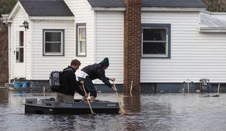 People navigate flooding on Phoenix Street in Niles, Mich., Thursday, Feb. 22, 2018. (Mark Bugnaski/Kalamazoo Gazette-MLive Media Group via AP)