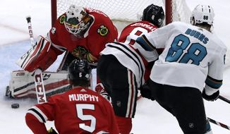 Chicago Blackhawks goalie J.F. Berube, left, blocks a shot by San Jose Sharks defenseman Brent Burns, right, during the first period of an NHL hockey game Friday, Feb. 23, 2018, in Chicago. (AP Photo/Nam Y. Huh)